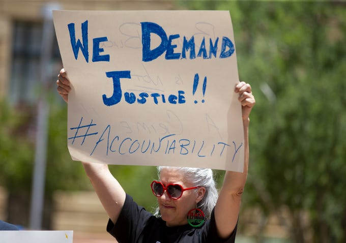 Ramona Ferrara, of Phoenix, protests recent actions of the Phoenix Police Department, which many view as racist and an example of police brutality.