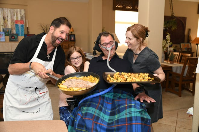 Volunteer Jeff Riddle plays chef for Hospice of the Valley ALS patient Mark Adinolfi, wife Jeane and daughter Sophia.