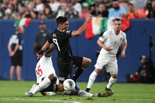 El atacante Raúl Jiménez trata de eludir la marca de un defensivo canadiense.