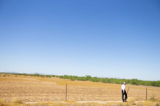 """Peter Hyde, profesor adjunto de investigación de la Universidad del Estado de Arizona que estudia los peligros cada vez mayores de soplar el polvo, camina por un campo en el condado de Pinal. """"El futuro no es brillante para las tormentas de polvo"""", dice Hyde. """"Van a empeorar y habrá más de ellas""""."""