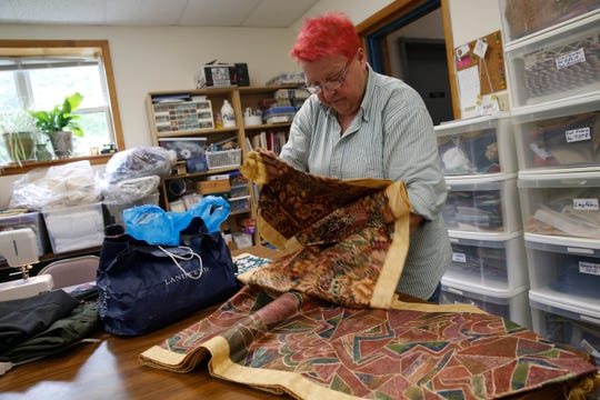 Sewing room volunteer Sue Cornell folds table runners that she and fellow Red Hook Community Center volunteers sewed for the center's upcoming gala in Red Hook on June 19, 2019.
