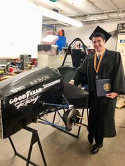Poughkeepsie native Sean Sheridan poses next to the electric race car he helped build on graduation day from the University of Akron in May.
