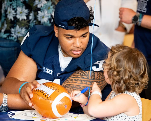 PJ Mustipher (93) talks with a little fan during the Penn State football team's annual visit to the Milton S. Hershey Medical Center, June 19, 2019.