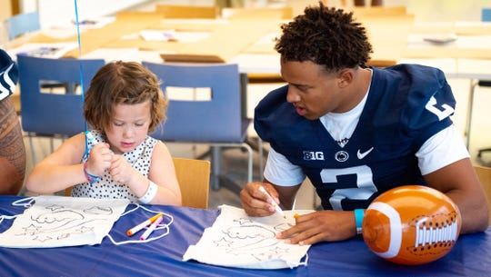 Keaton Ellis (2) and Devin Pulaski, 6, of Palmyra draw during the Penn State football team's annual visit to the Milton S. Hershey Medical Center, June 19, 2019.
