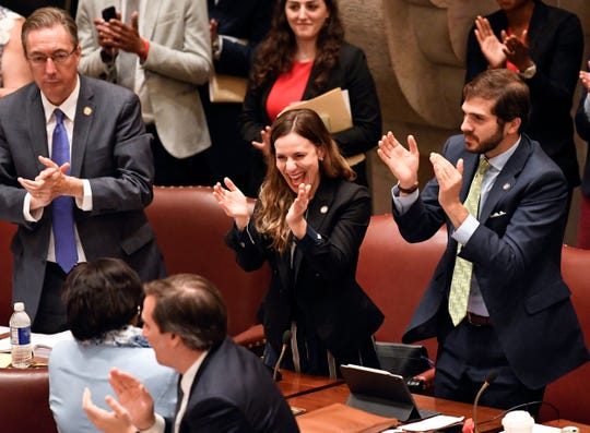 New York Sen. Alessandra Biaggi, D-Bronx, center, celebrates after her legislation passed to change state legal standards on sexual harassment to help victims prove harassment cases, as members discuss the bill in the Senate Chamber at the state Capitol, Wednesday, June 19, 2019, in Albany, N.Y.