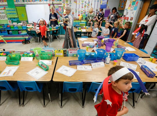 Volunteer Darlene Anderson waves an American flag as she marches around the classroom with kindergarten students at McBride Elementary School in Springfield, Mo., on Thursday, June 20, 2019.