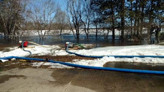 Pumps clear water from Greg Rakotz's Haven township backyard in March 2019. He says the water flowed from the construction site of a new solar garden behind his home.