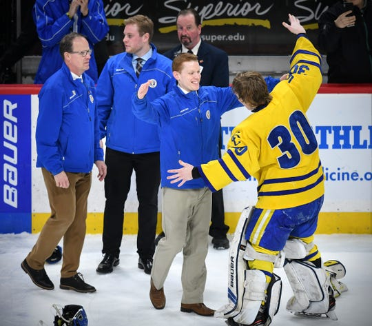 Cathedral head coach Derrick Brown celebrates with goaltender Noah Amundson following the state Class 2A championship game Saturday, March 9, 2019, at the Xcel Energy Center in St. Cloud.