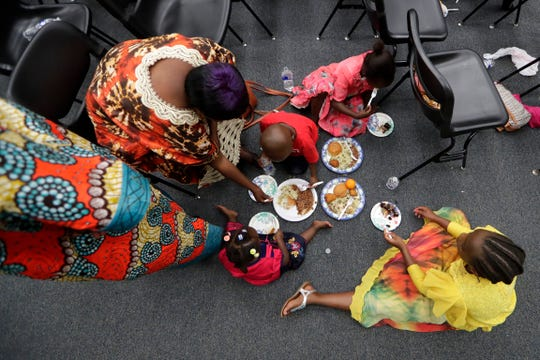 Children gather in a circle on the floor to eat lunch. World Refugee Day celebrated at the Adult & Community Education School welcomes refugees who have come to America for refuge from war and oppression Thursday, June 20, 2019.