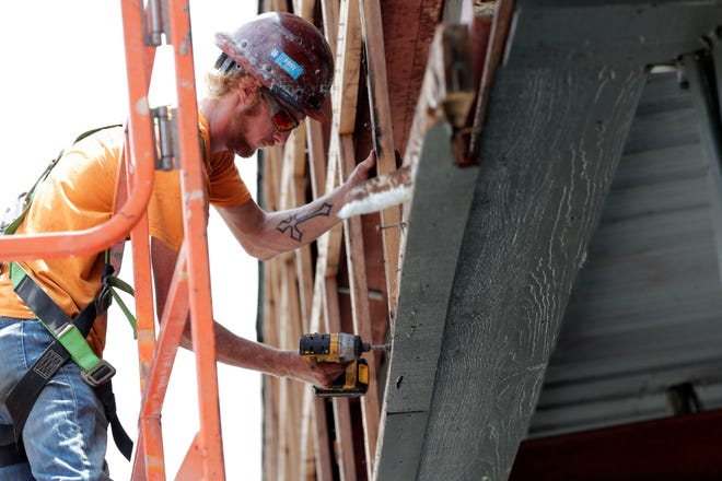 A worker with Great Southern Demolition uses a drill to remove the outer shell of Market Square as the area is being remodeled.