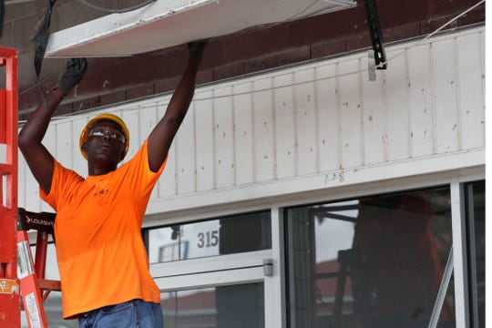 A worker with Great Southern Demolition takes off the outer shell of Market Square as the area is being remodeled.
