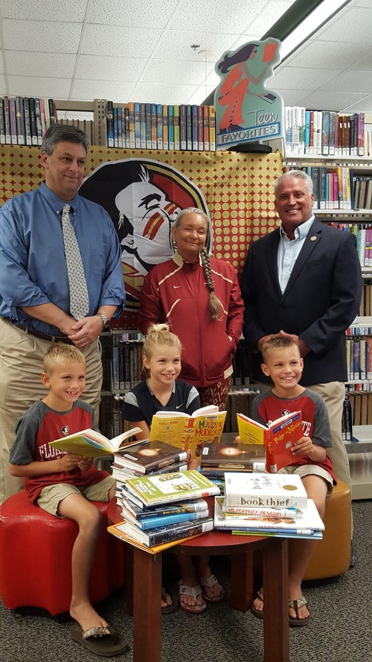 Fairlawn Elementary School students Logan, Georgia and Drew Myers, seated, enjoy new books donated to the St. Lucie County Library System by the Treasure Coast Seminole Club. Also pictured are, from left, standing, Mark Freed, head of Branch Libraries; Pam Punkar, former Treasure Coast Seminole Club officer, and County Commissioner Chris Dzadovsky.
