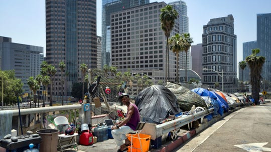 In this May 10, 2018, file photo, a homeless person sits at his tent along the Interstate 110 freeway downtown Los Angeles. Mayor Eric Garcetti is paying a political price for the city's homeless crisis. An effort is underway to recall the two-term Democrat from office prompted by widespread complaints about homeless encampments throughout the city.