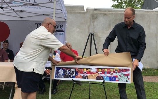 Russell Swanson, (right) helps artist George Perez unveil his concept for mural to be painted in Torpedo Park on Landis Avenue. June 20, 2019.