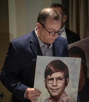 """Jonathan Chenkin, a childhood sex abuse victim, holds a picture of himself at age of his alleged abuse as he arrives for a press conference, Thursday, June 20, 2019, in New York. Over 200 survivors, including Chenkin, said that for more than 40 years Reginald Archibald, a pediatric endocrinologist and researcher who worked for Rockefeller University, used his position to abuse children as young as 2 years old. """"For three years I saw Dr. Archibald, a pedophile masquerading as a researcher of child growth and development,"""" said Chenkin."""