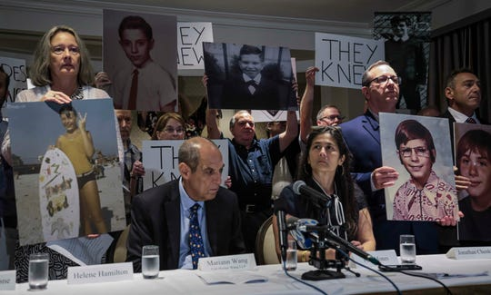 Childhood sex abuse victims and their lawyers arrive for a press conference, holding signs and photos of themselves at the age of their abuse, Thursday June 20, 2019, in New York. Attorneys Mariann Wang, third from right, and Paul Mones, fourth from right, second from left seated, representing over 200 survivors, allege that for more than 40 years Reginald Archibald, a pediatric endocrinologist and researcher who worked for Rockefeller University, used his position to abuse children as young as 2 years old.