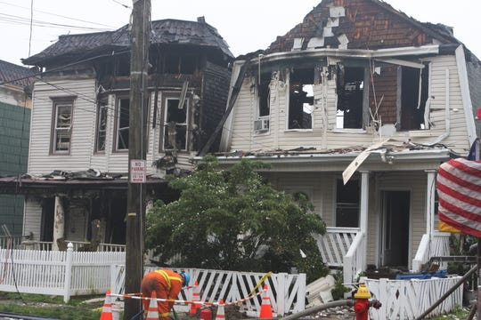 A Con Ed employee works at the scene of a fire that wrecked two houses on Warburton Avenue in Yonkers on June 19, 2019.
