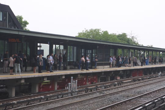 People wait for a New York City-bound Metro-North train at the Greystone station in Yonkers on June 20, 2019.