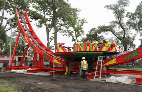 Workers assemble a new ride called Disk'O 24, manufactured by Zamperla at Playland in Rye, June 20, 2019.  The spinning ride should be ready by the end of July.