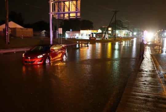 Cars are left stalled after rains overwhelmed culverts and flooded Del. 9 (New Castle Avenue) at the Interstate 295 interchange late Wednesday.