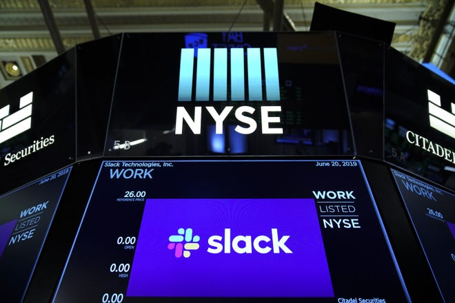 The logo for Slack is displayed on a trading post monitor at the New York Stock Exchange (NYSE), June 20, 2019 in New York City. The workplace messaging app Slack will list on the New York Stock Exchange this morning. Shares of Slack were surging more than 60 percent over its reference price in early afternoon trading.