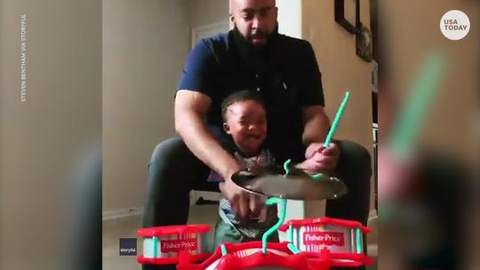 Toddler can't stop giggling while rocking out on the drums with dad