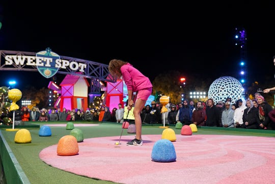 A competitor putts on the colorful, elaborate, architecturally complex miniature golf course on ABC's 'Holey Moley.'