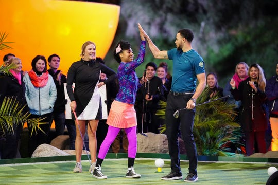 """NBA star - and """"Holey Moley"""" resident golf pro - Stephen Curry, right, shares a high-five with a competitor on the ABC extreme mini-golf series."""
