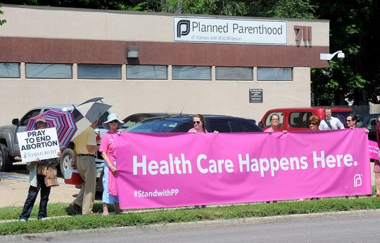 A man holding a sign who refused to give his name, left, stands next to five women holding a large banner supporting Planned Parenthood of Kansas and Mid-Missouri in July 2015 in front of the Planned Parenthood in Columbia, Mo. About 40 abortion rights supporters and 70 anti-abortion supporters stood in front of the clinic holding signs as anti-abortion speakers, including Mo. Rep. Diane Franklin and then Missouri gubernatorial candidate Catherine Hanaway called on state and federal officials to investigate and defund Planned Parenthood.