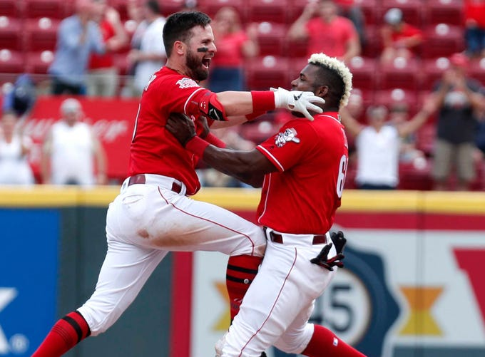 June 19: Jesse Winker, left, celebrates with Yasiel Puig after driving in the game-winning run to beat the Astros.