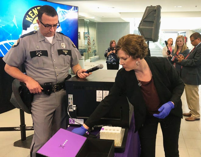 In this April 10, 2019, file photo, Regina Wells, foreground right, a forensic laboratories supervisor with the Kentucky State Police, demonstrates new crime-fighting technology in Frankfort, Ky.