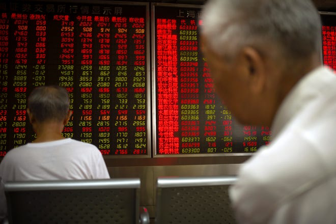 Chinese investors monitor stock prices at a brokerage house in Beijing.