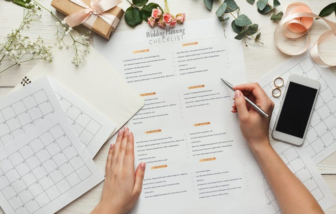 Wedding background with checklist and calendar. Female hands arranging marriage, filling in planners on white wooden table with lots of tender bridal stuff, top view