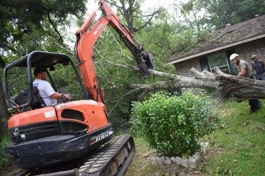 "David ""Uno"" Lay (left) and Braydan Daugherty, both member of the United Cajun Navy out of Baton Rouge, clear away tree limbs from a tree that fell on Carmen and Derick Cheek's house located on Springhill Road in Ball. The United Cajun Navy is in town to help the Cheeks and other storm victims clear away trees and other damage to property."