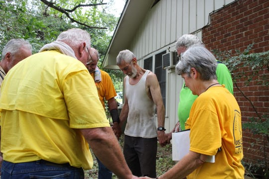 Reggy Saxon (left) leads a prayer Friday afternoon for Paul Karisny (center), whose Ball home was damaged early Thursday by a tornado. Saxon and a Southern Baptist Disaster Relief crew plan to be in the area for a few days. Shirley Hudson (right) has a Bible tucked under her arm that she gave to Karisny after the prayer.