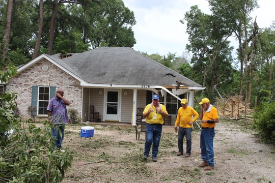 Reggy Saxon (center) looks around a house on Ball Loop Friday that was heavily damaged by an early Thursday tornado. He and his Southern Baptist Disaster Relief crew were surveying to see how they might be able to help on Saturday.