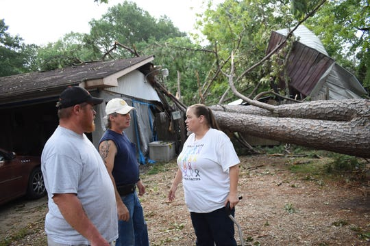 "David ""Uno"" Lay (left), a member of the United Cajun Navy out of Baton Rouge, talks to Derick and Carmen Cheek. The United Cajun Navy is in the area to help storm victims clear away storm damage and debris."