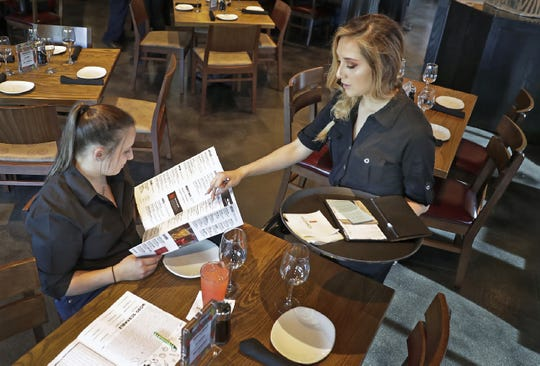 Bartender Alexis Ferland, left, plays the part of customer for server Lili Aguilar during staff training at P.F. Chang's in Grand Chute. The restaurant opens June 24.