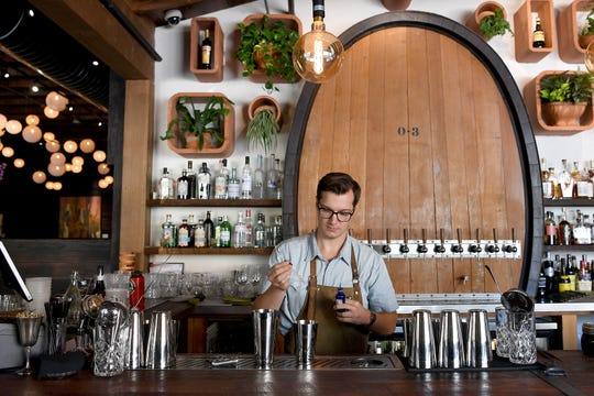 Nick Brodd crafts a cocktail behind the bar at Cultura on Asheville's South Slope on June 20, 2019.