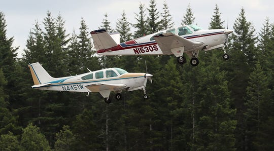 """A pair of planes take off in formation from the runway during the Northwest Formation Flying Clinic at the Bremerton National Airport on Friday. Nearly 40 pilots are participating in the clinic to learn to fly in formation, with many preparing to fly in the annual """"Bonanzas to Oshkosh"""" event in Wisconsin in July."""