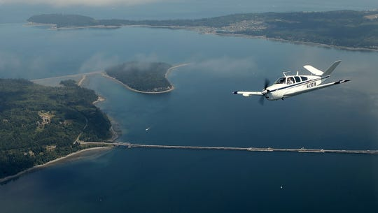 "Matthew Nash, of Edmonds, pilots his Beechcraft Bonanza high above the Hood Canal bridge while taking part in the Northwest Formation Flying Clinic on Friday. Nash — a newcomer to formation flying who was being coached by experienced formation pilot Mark Merrill in the co-pilots seat — was flying in the ""wing"" position."