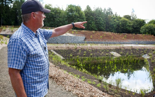 Chris May of Kitsap Public Works explains how stormwater is cleaned through the bio-retention cells then flows into the ponds before being carried back to Clear Creek.