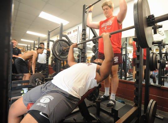 Owen rising senior Jaylin Davidson bench presses 225 pounds as teammate and fellow lineman Eli Brasher spots him.