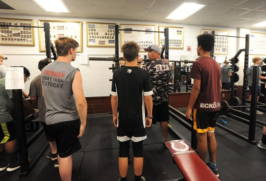 Warhorse head coach Nathan Padgett demonstrates proper technique in the weight room at Owen.