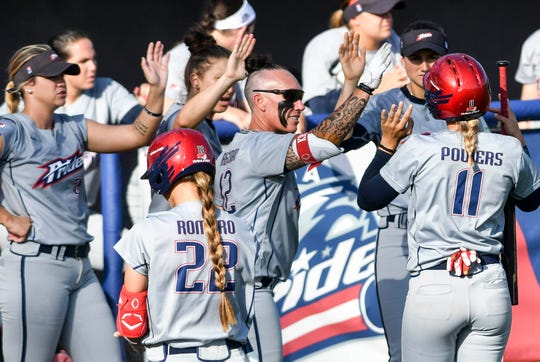 Alex Powers gets high fives from her Pride teammates after scoring in Thursday's doubleheader at Space Coast Stadium.