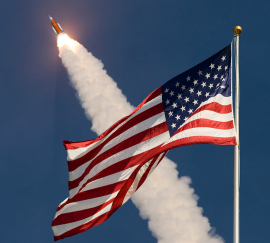 A rendering of NASA's Space Launch System rocket lifting off with an American flag in the foreground.