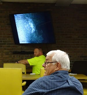 Lyn Makeever of Makeever & Associates, right, addresses members of Bucyrus City Council while John Ernsberger of the city's water department shows a video of the interior a 24-inch raw water line during a meeting of council's service committee on Thursday evening. The white spot on the pipe's interior will require further investigation if council decides to move ahead with plans to use the line for clean water.