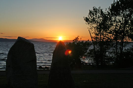 The sun sets on the Burlington Earth Clock, which features a stone circle and sundial. June 2009.