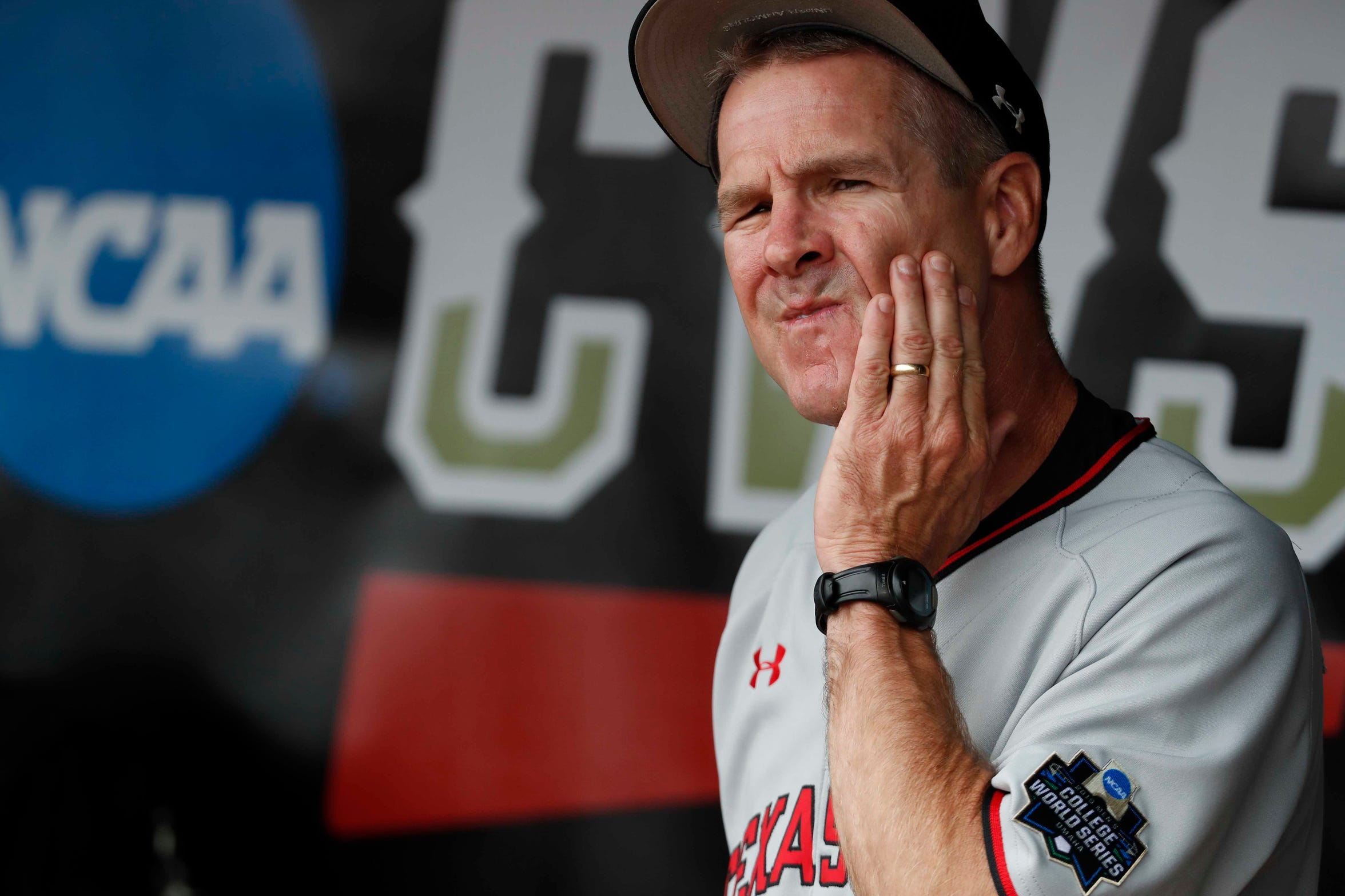 Texas Tech Red Raiders head coach Tim Tadlock cubs his face prior to the game against the Michigan Wolverines in the 2019 College World Series at TD Ameritrade Park.