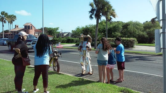 A crowd gathers around Ronald Mathis at a park on Ocean Drive.
